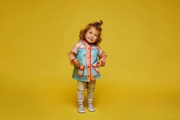 黄色の背景で分離されたモダンなレインコートとゴム長靴でかわいい女の子。子供のファッション。コピースペース