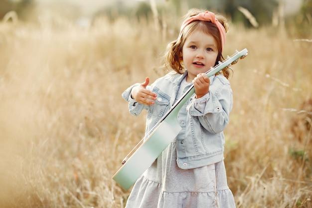 Милая маленькая девочка в парке играет на гитаре