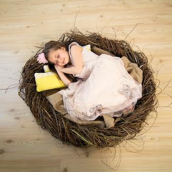 Милая маленькая девочка в розовом платье и розовой короне спит в большом гнезде и видит сказочные сны.
