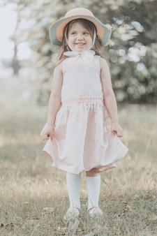Милая маленькая девочка в розовом платье с шляпой стоит в парке летом. фото высокого качества
