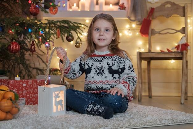 クリスマスツリーでスカンジナビアのセーターを着たかわいい女の子。クリスマスと新年の家族のお祝いの概念