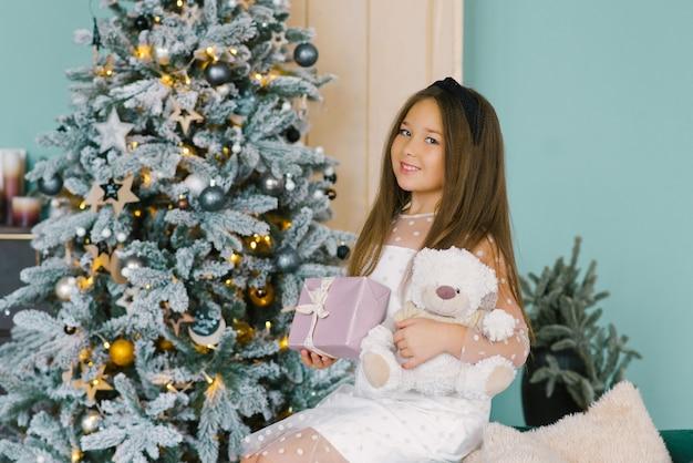 집에 크리스마스 선물 상자가 있는 똑똑한 흰색 얇은 명주 그물 드레스를 입은 귀여운 소녀
