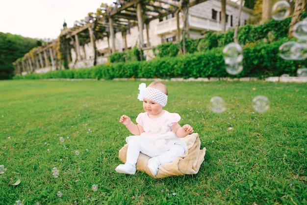 나비가 달린 흰색 붕대를 입은 귀여운 소녀가 정원에 있는 담요에 앉아 있습니다. 잔디 주변에는 많은 비눗방울이 있습니다. 빌라 마일로체르, 몬테네그로. 고품질 사진