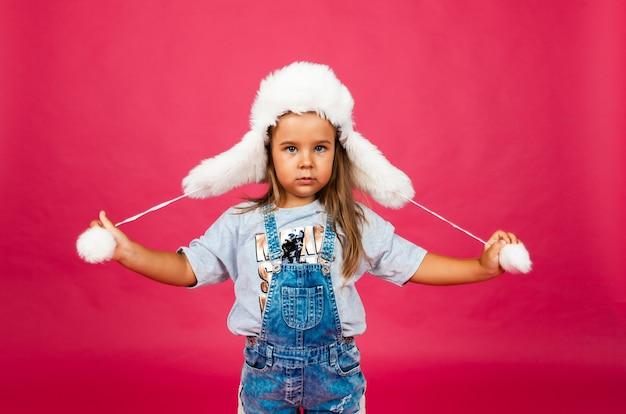 ピンクの壁に白い毛皮の帽子をかぶったかわいい女の子。ファッションコンセプト。