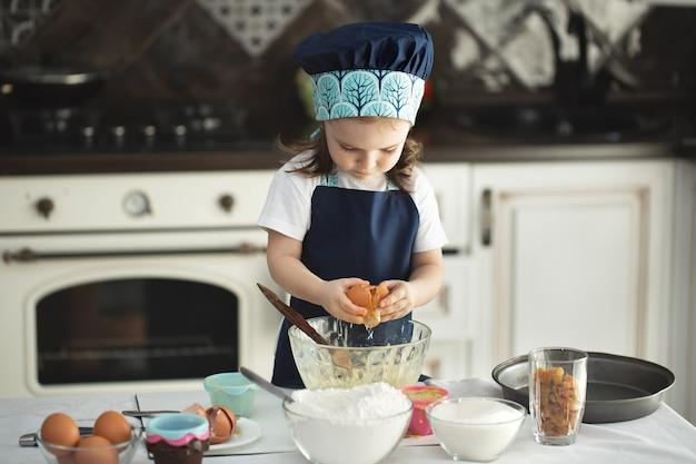 エプロンとシェフの帽子をかぶったかわいい女の子が卵を皿に割る