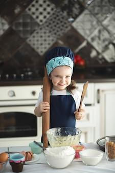 エプロンとシェフの帽子をかぶったかわいい女の子がめん棒を使って生地を平らにしている