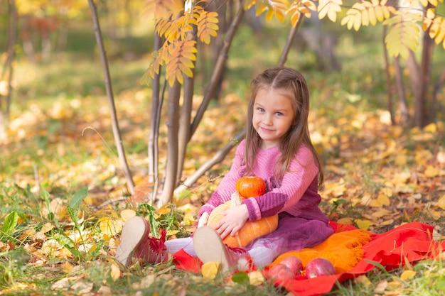 Милая маленькая девочка в осеннем осеннем парке с оранжевыми листьями и желтой тыквой