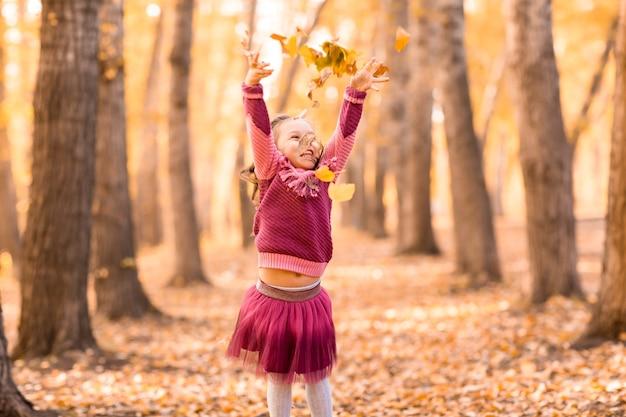 Милая маленькая девочка в осеннем парке подбрасывает листья оранжевого и желтого цвета. осень.