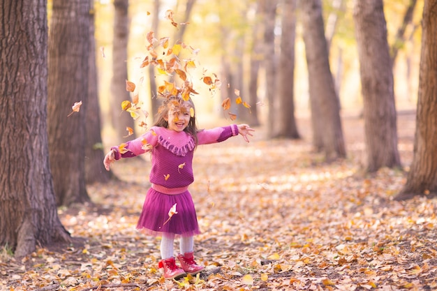 Милая маленькая девочка в осеннем парке с оранжевыми и желтыми листьями