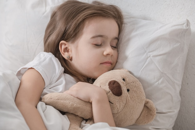 ぬいぐるみとベッドでかわいい女の子