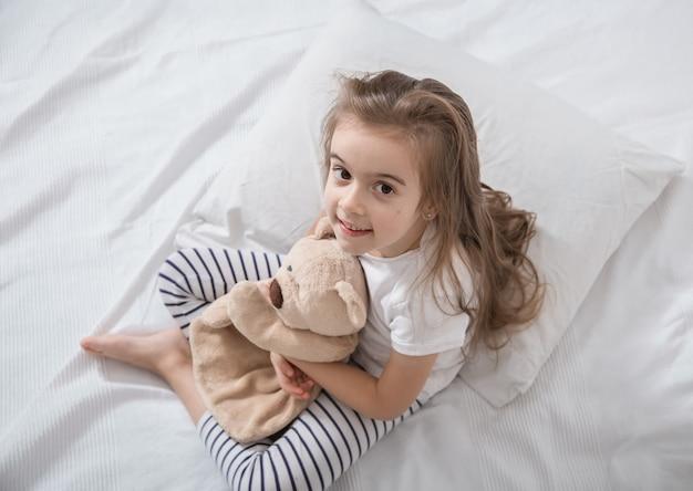 Милая маленькая девочка в постели с мягкой игрушкой.