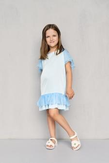 파란 드레스와 흰색 샌들 회색 벽 근처에 포즈에 귀여운 소녀