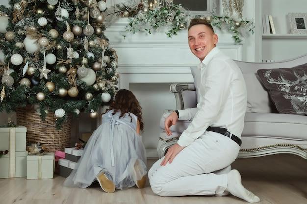 クリスマスのリビングルームで青いドレスを着たかわいい女の子が幸せそうに笑っているお父さんと遊んでいます。クリスマスの瞬間、新年あけましておめでとうございます、子供の頃の瞬間の概念。雰囲気のある家族の瞬間。コピースペース