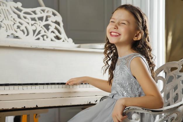 古いアンティークのグランドピアノを弾き、幸せそうに笑っている青いドレスのかわいい女の子。ピアノを弾くことを学ぶという概念と幸せな子供の頃の瞬間。雰囲気のある家族の瞬間。サイトのコピースペース