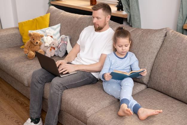 青いパジャマを着たかわいい女の子がソファに座っておとぎ話を読んでいる間、ラップトップを持った父親が検疫期間中にリモートで作業しています