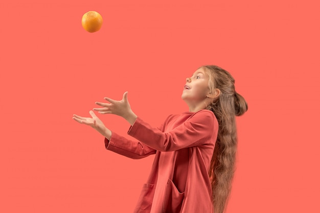 オレンジで遊んで長い髪のサンゴのドレスでかわいい女の子