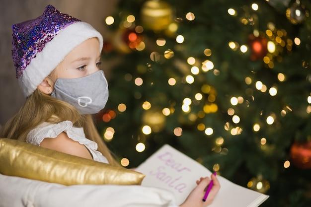 クリスマスツリーの近くのサンタクロースに手紙を書いている顔のマスクのかわいい女の子