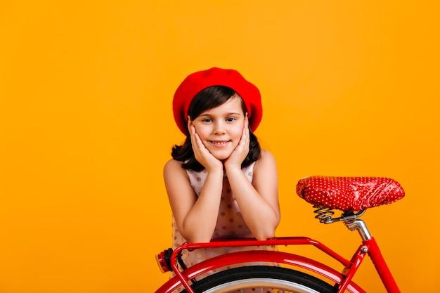 프랑스 베레모 자전거와 함께 포즈를 취하는 귀여운 소녀. 노란색에 고립 된 웃는 아이.