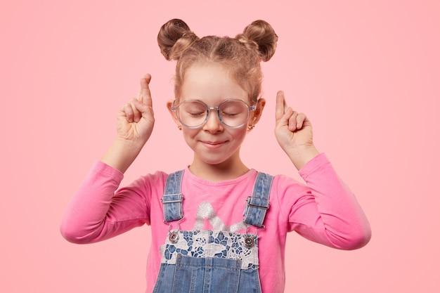 눈을 감고 손가락으로 안경과 캐주얼 옷을 입은 귀여운 소녀가 서있는 동안 소원을 빌었습니다.