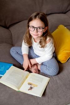Милая маленькая девочка в очках, джинсах и белой водолазке делает домашнее задание, сидя на кровати