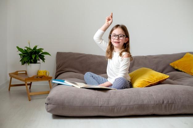 Милая маленькая девочка в очках, джинсах и белой водолазке готовится к экзаменам, сидя на кровати