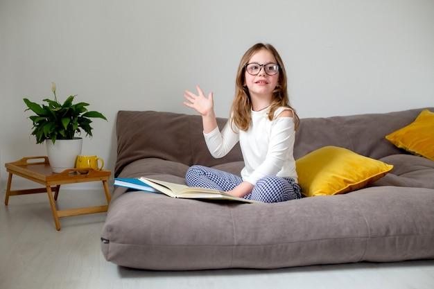 Милая маленькая девочка в очках, джинсах и белой водолазке читает книгу, сидя на кровати