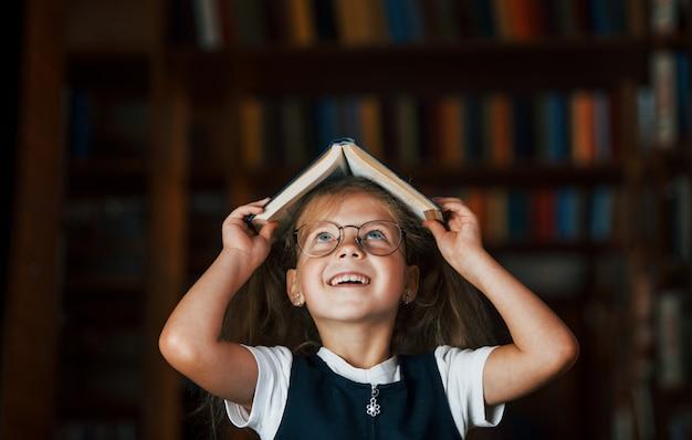 Милая маленькая девочка в очках стоит в библиотеке, полной книг