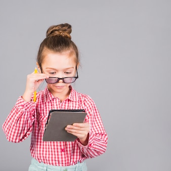 Милая маленькая девочка в очках с помощью планшета
