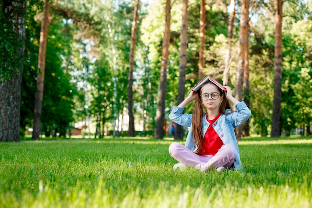 Милая маленькая девочка в очках с книгой на голове в летнем парке