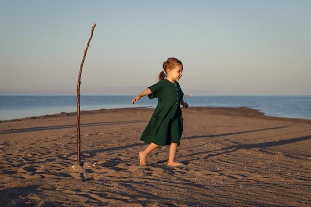무인도의 해변에서 놀고 있는 녹색 드레스를 입은 귀여운 소녀.
