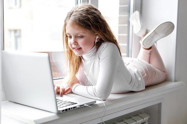 オンライン教育と自宅学習のために自宅でラップトップを使用してヘッドフォンでかわいい女の子