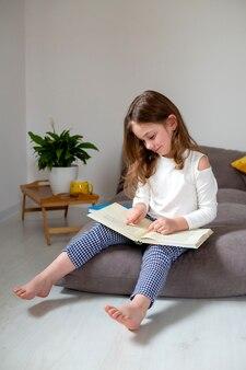 청바지와 흰색 터틀넥을 입은 귀여운 소녀가 침대에 앉아 책을 읽고 숙제를 하고 있다