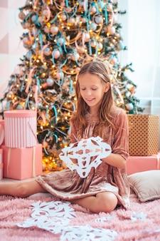 Милая маленькая девочка в гостиной лепит бумажные снежинки
