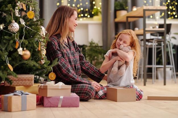 Милая маленькая девочка в пижаме обнимает плюшевого медвежонка, сидя на полу рядом с мамой у украшенной елки в рождественское утро
