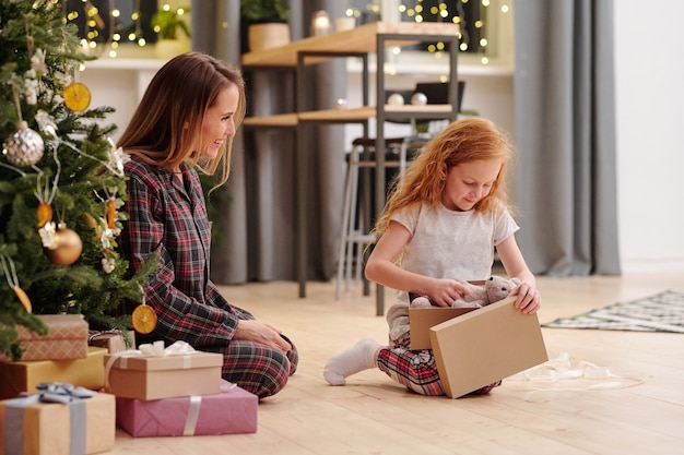 クリスマスの日に飾られたモミの木によって彼女の母親の隣の床に座っている間、ギフトボックスからテディベアを取り出しているパジャマのかわいい女の子