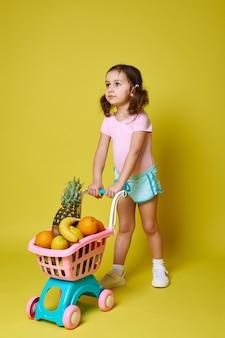 분홍색 바디 슈트와 파란색 반바지에 귀여운 소녀는 복사 공간이 노란색에 과일로 가득한 쇼핑 카트를 롤백합니다.