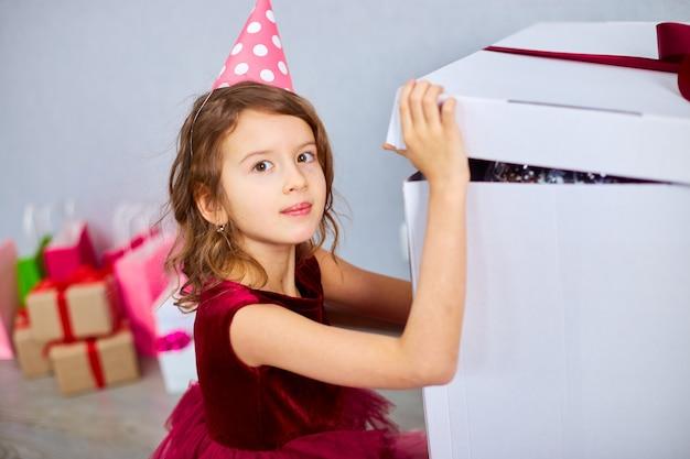 Милая маленькая девочка в розовом платье и шляпе открывает большую подарочную коробку