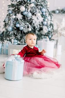 빨간 드레스에 귀여운 소녀는 크리스마스 트리 근처 바닥에 크리스마스 상자 선물로 활약