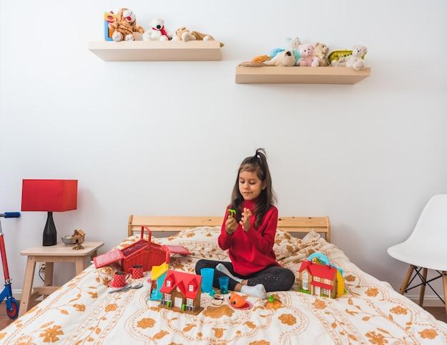 침실에서 그녀의 장난감을 가지고 노는 빨간색 긴 목 티셔츠 스웨터에 귀여운 소녀.