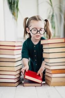 둥근 모양의 안경과 녹색 모슬린 드레스를 입은 귀여운 소녀는 다채로운 책을 순서대로 접습니다.