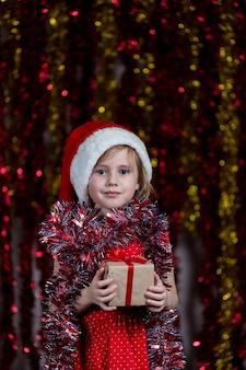 Милая маленькая девочка в шляпе санты и с мишурой на шее, держа подарок на новый год.