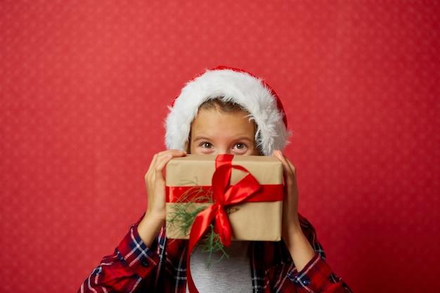 彼女の顔の前にクリスマスプレゼントを保持しているサンタ帽子のかわいい女の子