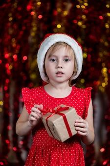 Милая маленькая девочка в шляпе санты держит новогодний подарок с удивленным лицом.