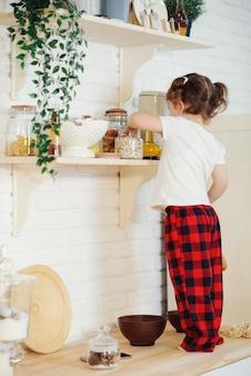 Милая маленькая девочка в шляпе санта, готовит печенье на кухне дома. садится на кухонный стол и помогает маме приготовить праздничный рождественский ужин