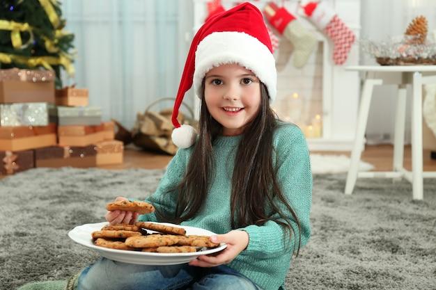 Милая маленькая девочка в шляпе санты с тарелкой вкусного печенья дома