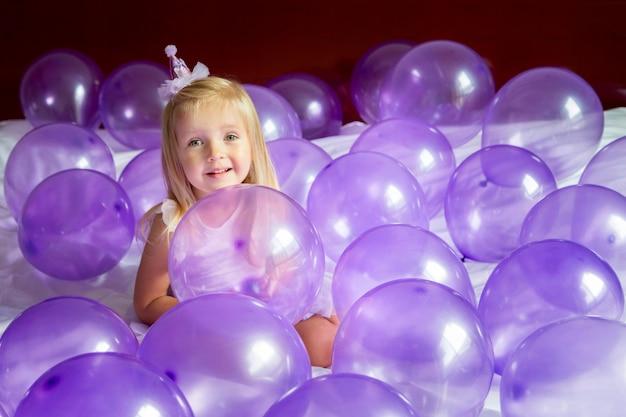 紫色の風船で誕生日を祝うスタイリッシュなドレスでかわいい女の子