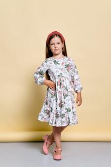 Милая маленькая девочка в сарафане и ободке для волос позирует в студии над бледно-желтым
