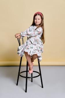 Милая маленькая девочка в сарафане и ободке для волос сидит на высоком стуле в студии над бледно-желтым
