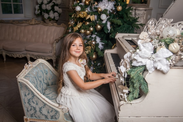 Милая маленькая девочка в белом платье играет на пианино на фоне украшенной елки.
