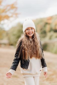 Милая маленькая девочка в белой шляпе и черной кожаной куртке осенняя фотография